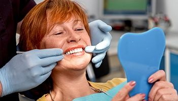 Senior woman in dental chair looking at smile