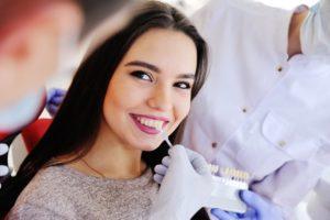 Woman smiling at porcelain veneer consultation