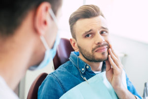 Man holding chin worried about dental implant failure in Los Angeles