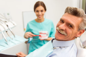Elderly man smiling in dentist's chair