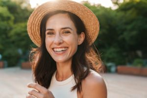 Woman smiling outside on a sunny day while wearing a hat